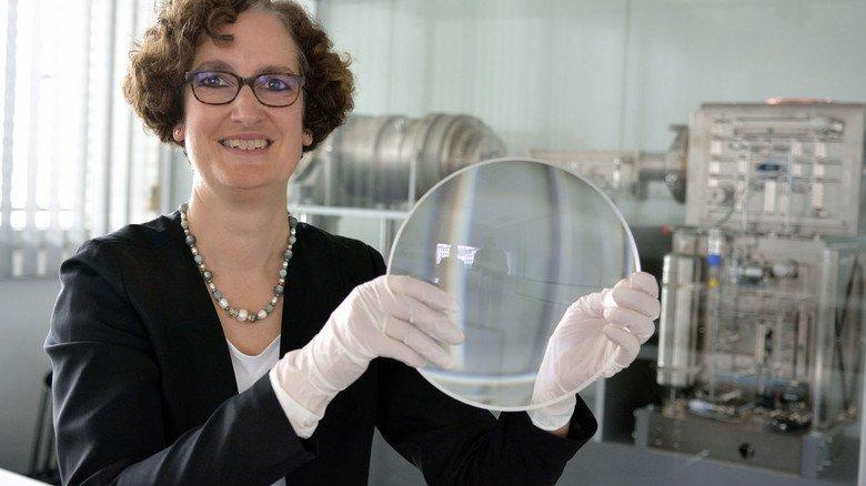 Durchblick im Nanometer-Bereich: Katrin Ariki, Standortleiterin der Zeiss-Halbleitersparte SMT in Wetzlar, zeigt eine Linse, die gleich zu mehreren in einer Maschine für die Halbleiter-Industrie steckt (im Bildhintergrund).