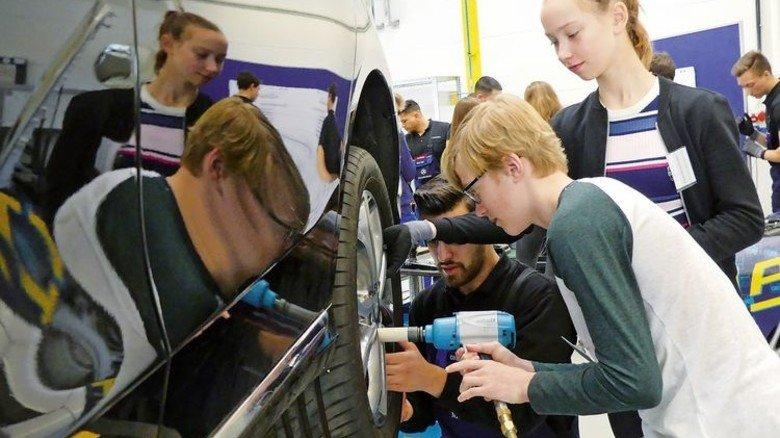 Lernen fürs Leben: Ein Mercedes-Azubi zeigt den Schülern, wie  nach einem Radwechsel die Schrauben angezogen werden müssen. Foto: Mercedes