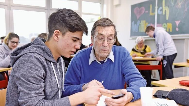 Individuelle Beratung: Für jeden Teilnehmer gibt es einen Schüler, der den Umgang mit Smartphones erklärt. Foto: Augustin