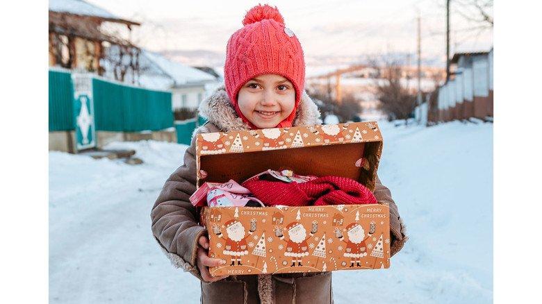 """Strahlende Augen: Dieses Mädchen aus Moldawien freut sich über ein prall gefülltes Geschenk-Päckchen der Aktion """"Weihnachten im Schuhkarton""""."""