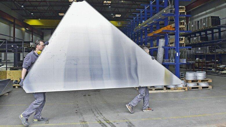 Bausatz: Zwei Mitarbeiter tragen ein zugeschnittenes Aluminium-Blech in den Versandbereich.