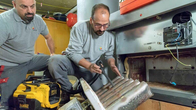 Heizungswartung: Handwerker beim Check einer Heizung. Wer jetzt neue Technik einbaut, kann enorme Zuschüsse bekommen.