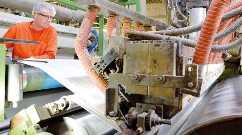 Vorsicht, heiß! Hier wird flüssiger Kunststoff auf die Papierbahn aufgebracht.          Foto: Scheffler