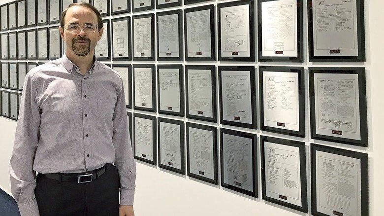 """Der Erfinder: Der Wissenschaftler Alexander Makarov vor der """"Wand der Patente"""". Rund 120 der über 370 Patente, die das Unternehmen hält, sind von ihm."""