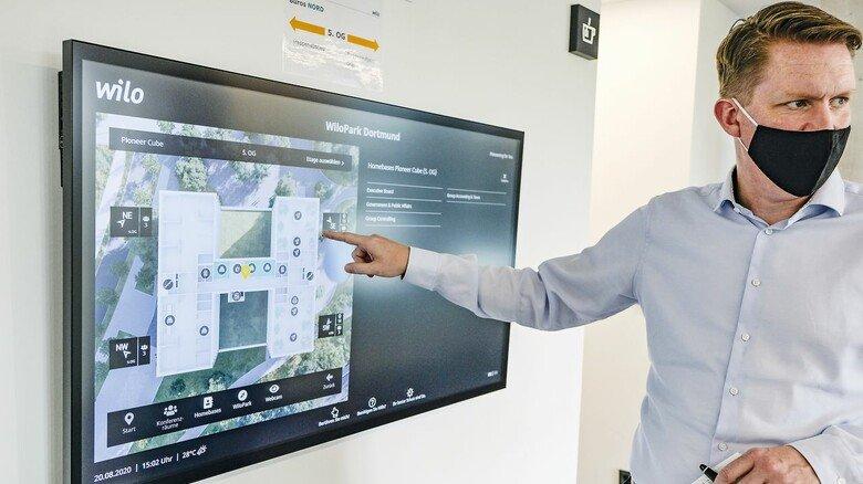 Wegweisend: Pressesprecher Klaus Hübscher zeigt, wie man an diesem Bildschirm einen verfügbaren Arbeitsplatz im neuen Verwaltungsgebäude bucht.