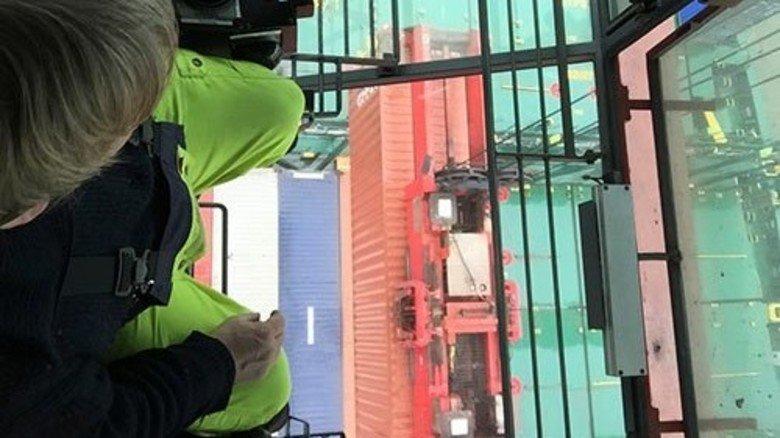 Arbeitsalltag: Der Kranfahrer sieht zwischen seinen Füßen die Container auf dem Frachter. Foto: Roth