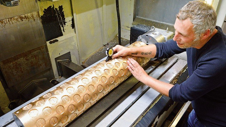 Zerspanungsmechaniker Jürgen Johannes kontrolliert die Tiefe des Musters in einer Gebäckformwalze
