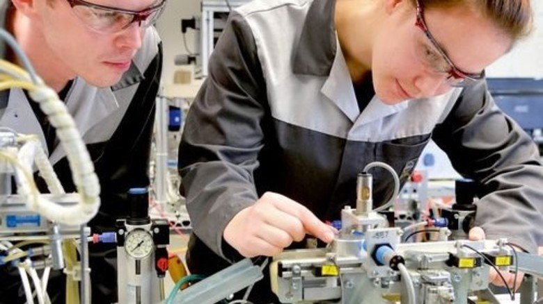 Steuern eine Minifabrik zum Lernen: Mechatronik-Azubi Jennifer Schubert und Meister Peter Minnert bei Opel. Foto: Scheffler