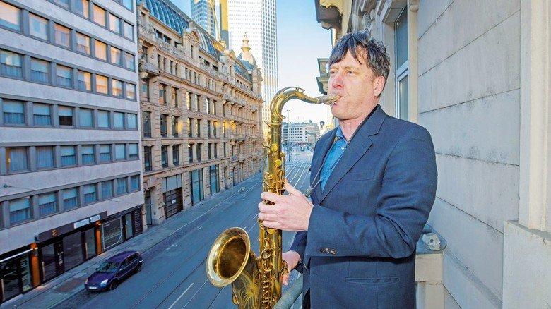 """Mut machen mit Musik: Der Saxophonist Tobias Rüger spielt auf einem Balkon in Frankfurt die """"Ode an die Freude""""."""