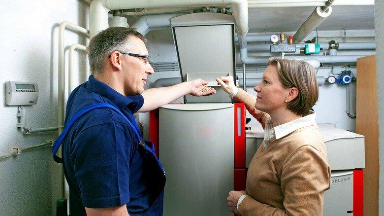 Pelletheizung: Ein Heizungsmonteur erklärt einer jungen Frau die Funktionsweise dieser Biomassen-Heizung. Beim Einbau gibt es 30 Prozent Zuschuss.
