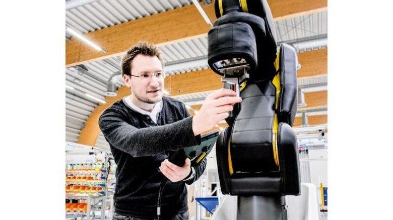 Ohne Schutzzaun: Sascha Heymann arbeitet Hand in Hand mit einem Roboter. Foto: Roth