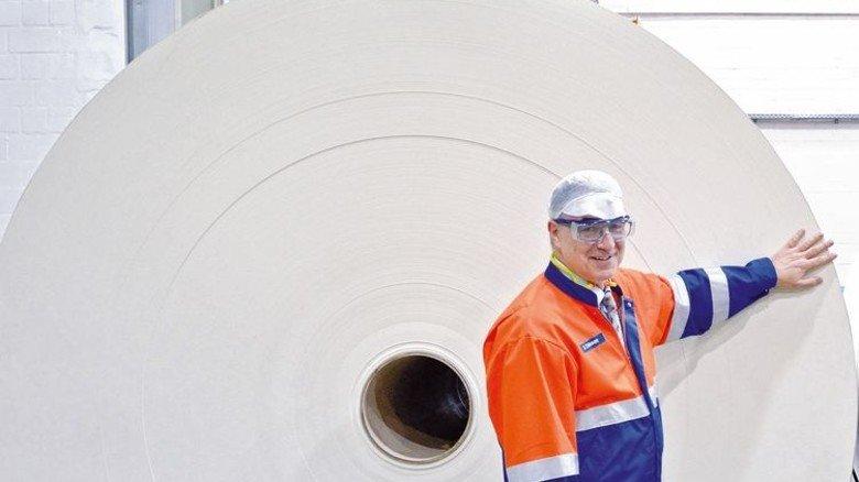 Wuchtige Ware: Wolfgang Thissen zeigt eine beschichtete Kartonrolle. Foto: Scheffler