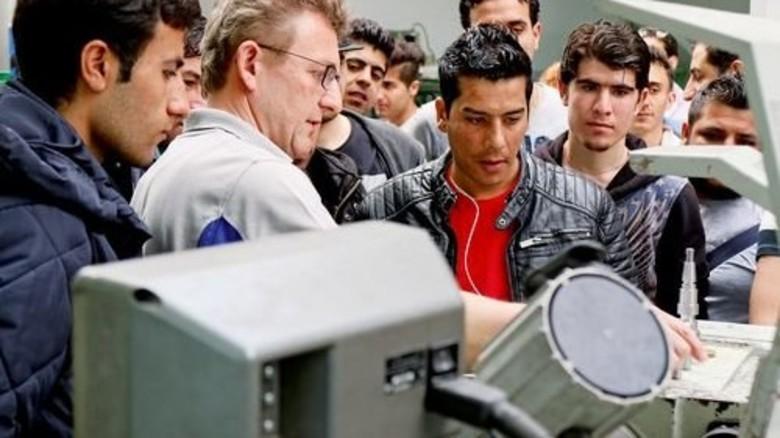 Neugierige Blicke: Werkstattleiter Andreas Jakubik vermittelt Flüchtlingen einen Eindruck von der Metallausbildung. Foto: Goor-Schotten