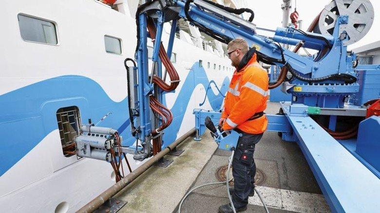 Maximal flexibel: Der Landstrom kommt über ein bewegliches Kabelsystem aufs Schiff. Foto: Christian Charisius/dpa