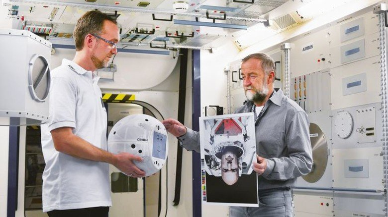 Lernfähig: Cimon prägt sich das Gesicht von Alexander Gerst ein. Gehalten wird der kleine Helfer von Projektleiter Till Eisenberg, Entwicklungsingenieur Josef Sommer zeigt ihm das Bild des Astronauten. Foto: Airbus