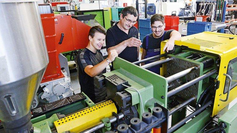Lernen an der Maschine: Ausbilder Peter Hohlfeld (Mitte) erklärt Diana Jurk (links) und Florian Werth, wie das Spritzgießen funktioniert.