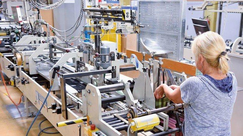 Produktiv: Eine Mitarbeiterin an einer Faltschachtelklebemaschine. Foto: Scheffler