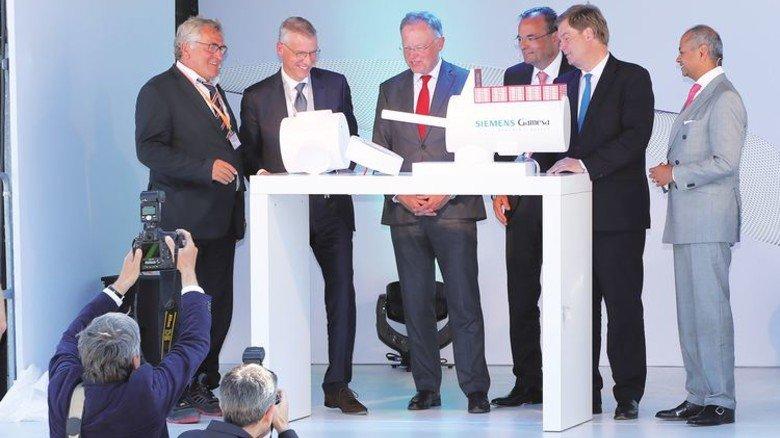 Eröffnungsfeier mit dem Landesvater: Niedersachsens Ministerpräsident Stephan Weil (Mitte) lässt sich an einem Modell die Fertigung von Maschinenhäusern für Offshore-Turbinen erklären. Foto: Siemens Gamesa/Ulrich Wirrwa