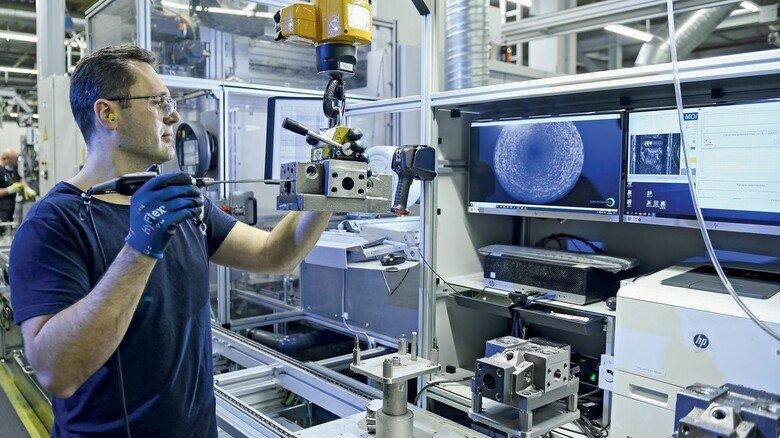 Tiefe Einblicke: Mitarbeiter Mantas Jochim inspiziert mit einer Stablupe die Bohrung im Inneren eines hydraulischen Bauteils.