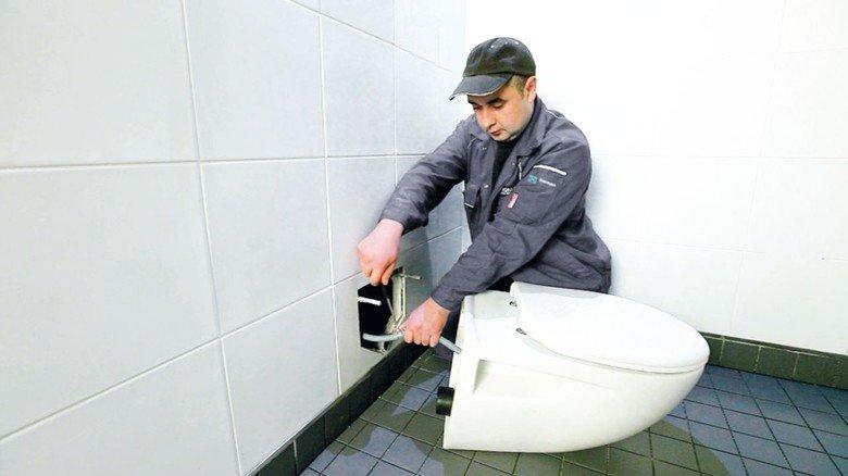Endmontage: Ein Handwerker beim Anschließen einer Vakuumtoilette.