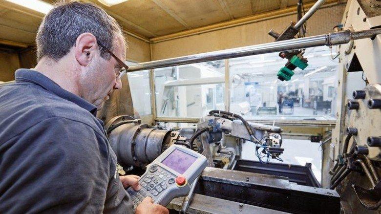 Feinarbeit: Nikolai Kesow richtet den Roboterarm einer Fertigungsstation neu ein. Foto: Thorsten Mischke