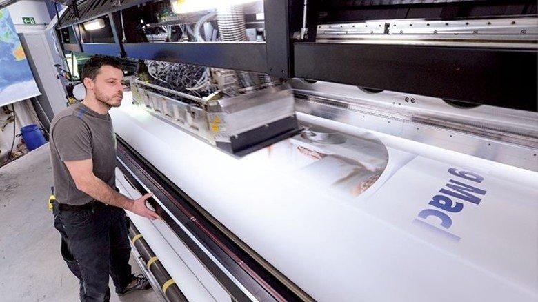 Moderne Technik: Bernd Rahmig überwacht den 120 Kilo schweren Druckkopf einer Digitaldruckmaschine. Foto: Sturm