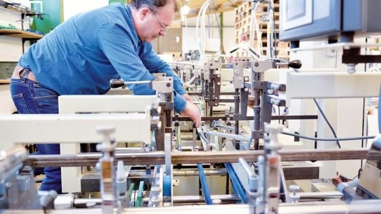 Umbau: Mieczyslaw Kròl beim Einrichten einer Klebemaschine. Foto: Scheffler