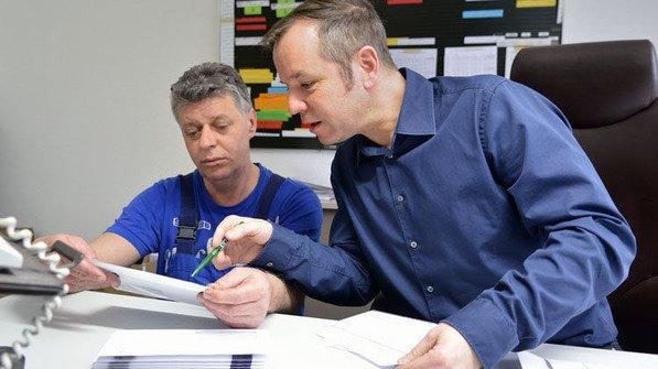 Kontrolle: Maschinen-Einsteller Robert Stieger und Attila Hezareh schauen sich eine Probe aus der gerade laufenden Produktion an. Foto: Scheffler