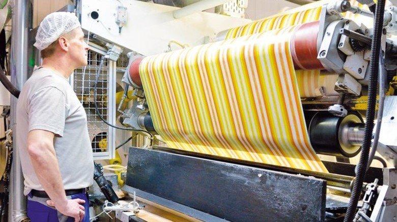 Spezialität: Maschinenführer Frank Frauendorf an einer Anlage, die Kaubonbon-Papier mit Wachs beschichtet. Foto: Scheffler