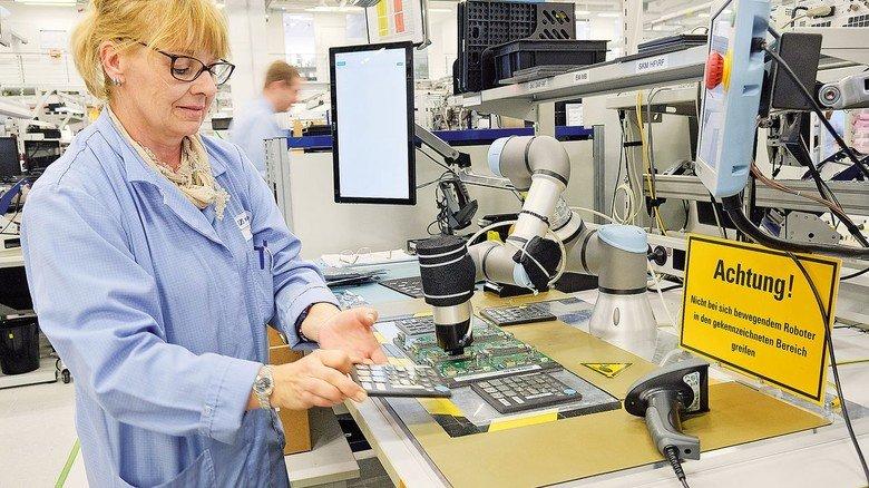 Eingespieltes Team: Ein Cobot nimmt Anja Bendiks mühsame Arbeit ab.