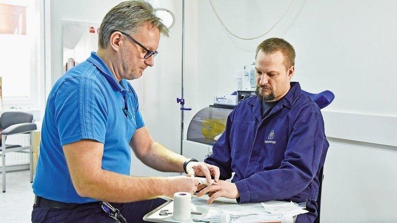 Erste Hilfe: TKMS-Sanitäter Andreas Greggersen verarztet einen Kollegen, der eine Wunde am Finger hat.
