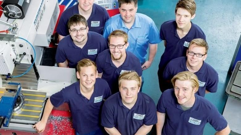 Nachwuchs: Ausbildungsleiter Michael Volmer (hellblaues Hemd) ist umringt von 8 der 14 gewerblichen Lehrlinge. Foto: Werk