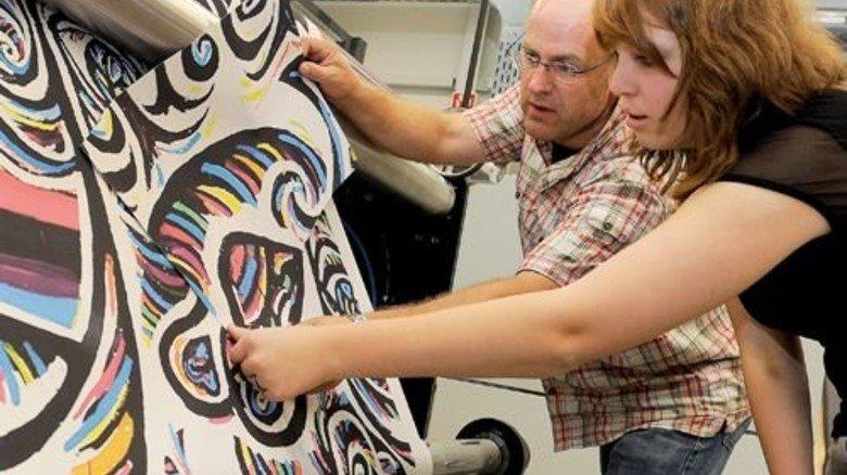 Originalgetreu: Volko Weyler und Azubi Sophie Schneider begutachten den Digitaldruck der Graffiti. Foto: Wirtz