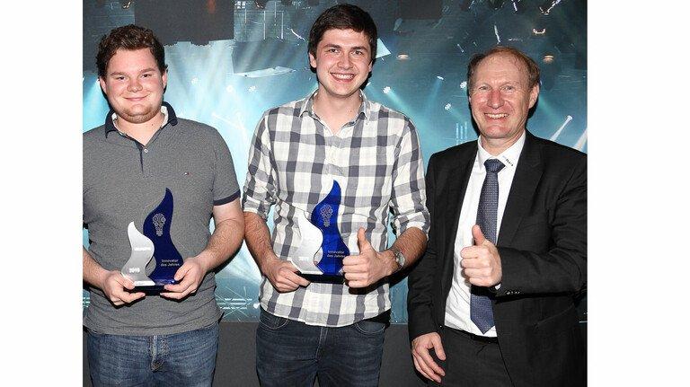 So sehen Sieger aus: Software-Entwickler Janik Siller (links) und Timo Dentler freuen sich über den Innovationspokal, überreicht von Rafi-CEO Dr. Lothar Seybold (rechts).