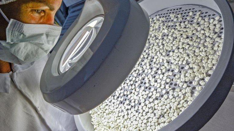 Pharmaproduktion bei Merck: Eine Mitarbeiterin kontrolliert den Lacküberzug von Tabletten. Foto: dpa