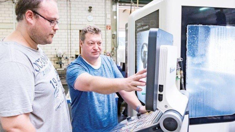 So geht's: Werkstattleiter Michael Einzinger (rechts) erklärt Marc Sporleder die Aufgabe an der CNC-Maschine. Foto: Heidrich