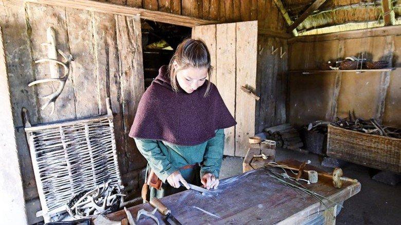 Wie vor tausend Jahren: Eine Haithabu-Museumsmitarbeiterin in historischer Kleidung. Foto: Carsten Rehder/dpa