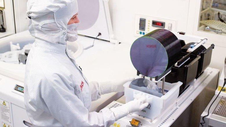 Produktion bei Bosch in Reutlingen: Eine Mitarbeiterin belädt eine Maschine mit Silizium-Rohlingen. Foto: Werk