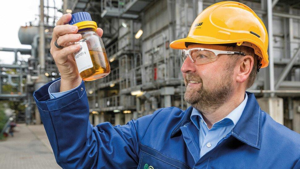 Andreas Kicherer, Sustainability Strategy, mit einer Flasche Pyrolyseöl, das aus Kunststoffabfällen zurückgewonnen wurde.
