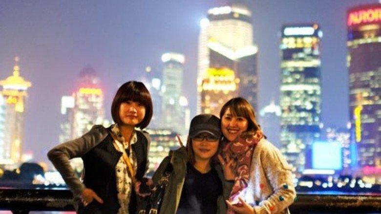 Jung und modern: Drei Chinesinnen posen vor der Skyline von Schanghai.  Foto: Roth