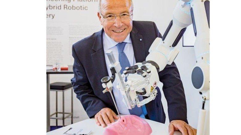 Das robotische Assistenzsystem der Münchener Firma Medineering unterstützt bei Hals-Nasen-Ohren-Operationen. Alfred Gaffal, vbw-Präsident und Vorsitzender des Zukunftsrats der Bayerischen Wirtschaft, schaut, wie es funktioniert. Foto: Schulz