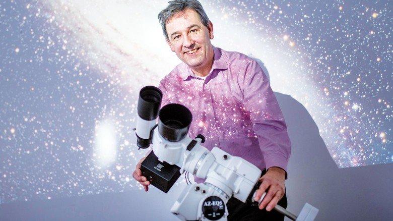 Stern-Stunden: Fotograf Holger Manz vor der Wandprojektion eines Fotos, das die  Andromeda-Galaxie zeigt.