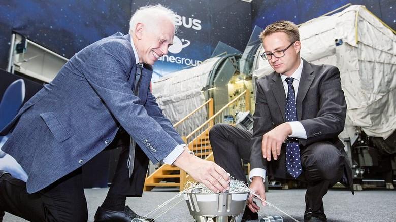 Airbus-Experten: Ingo Retat (links) und Robert Axthelm mit dem Gefäß, in dem das Netz steckt. Der Behälter wurde an Bord des Remove-Debris-Satelliten ins All geschossen. Foto: Lorenczat