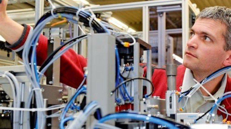Eigener Maschinenbau: Jochen Meyers justiert eine fertige Montageanlage. Foto: Wirtz