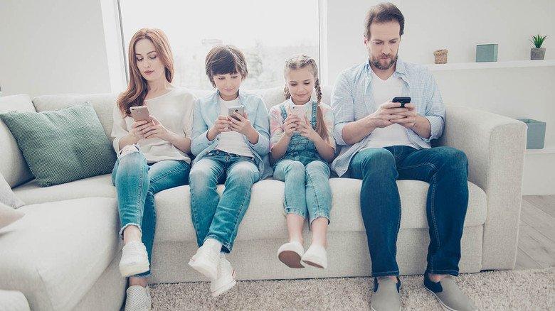 Familie mit Handy: Den Tarif sollte man immer auf das individuelle Nutzungsverhalten abstimmen.