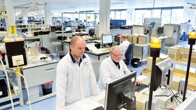 Produktion: Die Elektroniker Rolf Winter und Boris Weinsheimer (links) überprüfen Baugruppen für einen Cockpit-Rechner. Foto: Scheffler