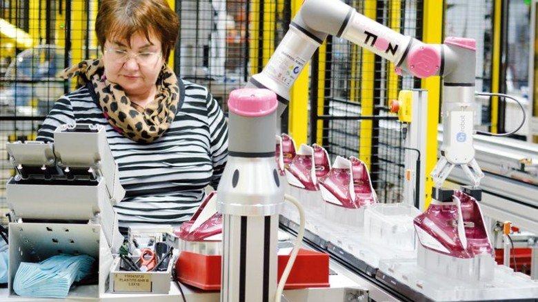 """Teamarbeit: Rosa Boll und ein """"Kobot"""" an der Linie der Spritzgussanlage. Foto: Scheffler"""