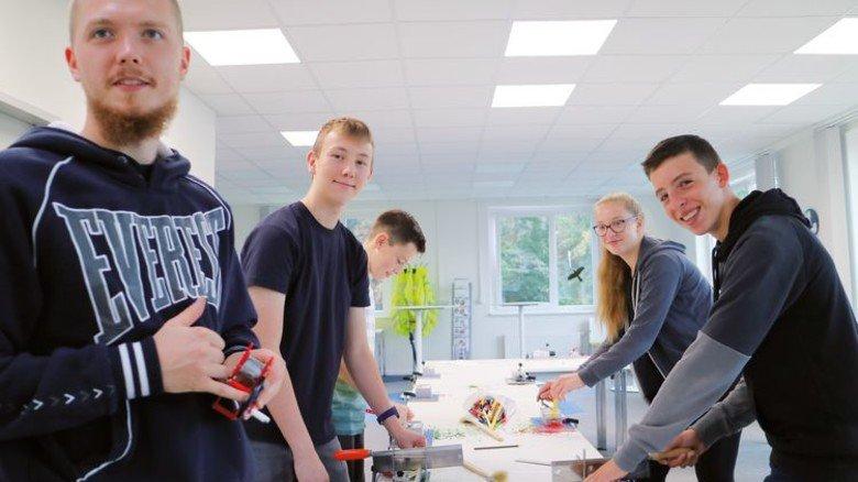 """""""MINT-Feriencamp"""": Lohmann-Azubi Leon Hüwel (links) half den Teilnehmern, eine Kurbelleuchte zu bauen. Foto: Higo"""