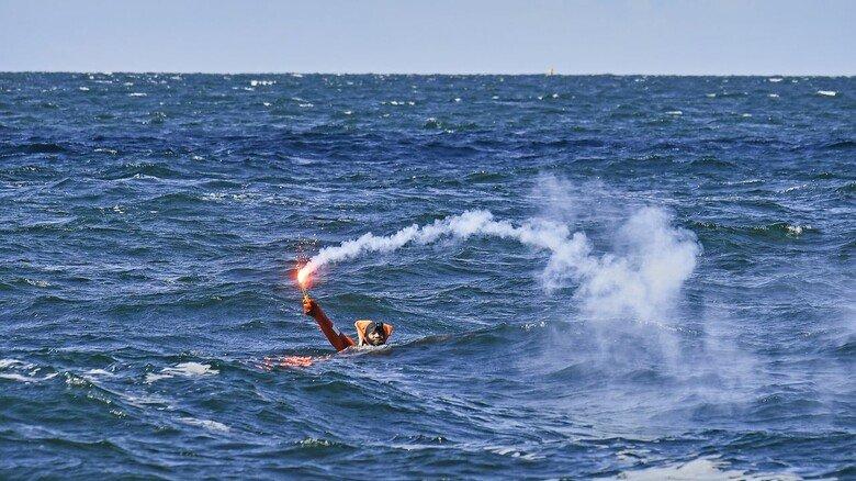 Warten auf Rettung: Ein Crewmitglied im Überlebensanzug zündet eine Leuchtfackel, damit der Hubschrauber-Pilot ihn im Wasser sehen kann.