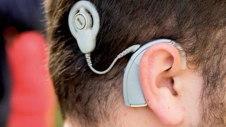 Hightech: Mikro am Ohr und ein Sender, der magnetisch an dem implantierten Empfänger haftet. Foto: Roth